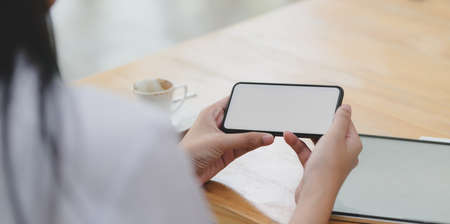 Close-up view of young female doctor looking at blank screen smartphone in her workspace