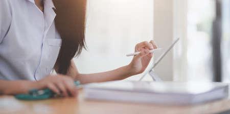Colpo ritagliato di una giovane dottoressa che esamina la cartella del paziente mentre usa il tablet nella sua stanza dell'ufficio