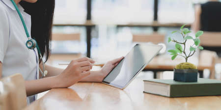Cropped shot of young female doctor examining medical report while using tablet