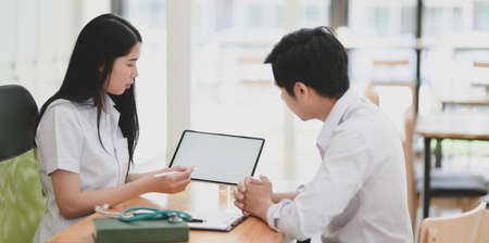 Close-up view of young professional female doctor explaining condition and symptoms to her patient