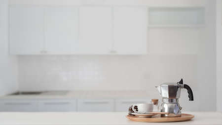 Coffee cup and Moka pot in wooden tray on white counter with blurred kitchen in the background