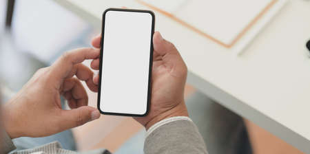 Close-up view of professional businessman holding blank screen smartphone in his office room