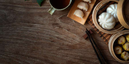 Top view of Chinese steamed dumpling and steamed pork bun in a bamboo steamer with chopstick on wooden table Foto de archivo