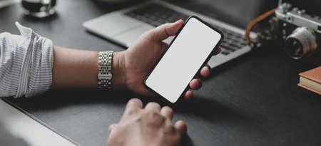 Bijgesneden opname van zakenman die een smartphone met een leeg scherm vasthoudt terwijl hij aan zijn project in zijn moderne kantoorruimte werkt Stockfoto