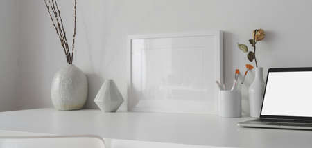 Minimal office room with mock up frame and open blank screen laptop computer on white table 스톡 콘텐츠