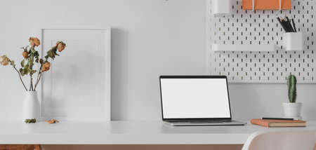 Modern workspace with open blank screen laptop computer and mock up frame with decorations on white wooden table