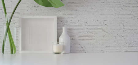 Mock up frame with decorations in minimal office room on white table and white brick wall background