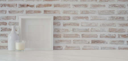 Minimal workspace with mock up frame and office supplies on white table with copy space and brick wall background 스톡 콘텐츠