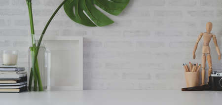 Comfortable workplace with mock up frame and office supplies on white table and white brick wall