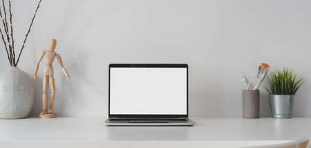 Open blank screen laptop computer in minimal workplace with decorations on white table and white wall background