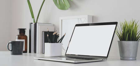 Cropped shot of modern office room with blank screen laptop computer and office supplies on white table