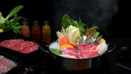 Close-up view of shabu shabu in hot pot with black background, fresh sliced meat, sea food and vegetables, Japanese hotpot style