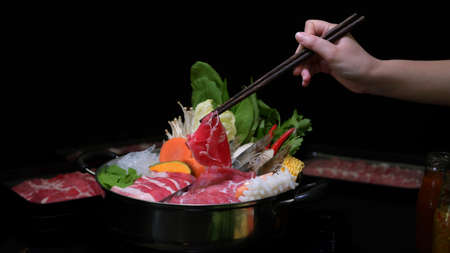 Cropped shot of woman eating Shabu-Shabu in hot pot with fresh sliced meat, sea food, and vegetables with black background, Japanese cuisine