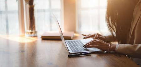 Abgeschnittene Aufnahme einer Geschäftsfrau, die an ihrem Projekt arbeitet, während sie auf einem Laptop in einem komfortablen Büroraum tippt Standard-Bild