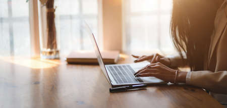 Scatto ritagliato di una donna d'affari che lavora al suo progetto mentre digita sul computer portatile in una comoda stanza dell'ufficio Archivio Fotografico