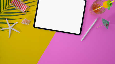 Colourful summer workspace with blank screen digital tablet on pink and yellow desk background
