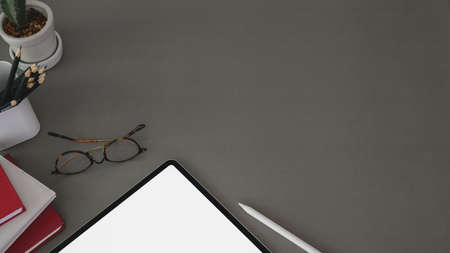 Top view of trendy workplace with tablet and office supplies on dark grey table background with copy space