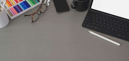 Overhead shot of modern designer workplace with digital tablet and office supplies on dark grey table background