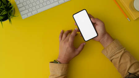 Top view of man holding blank screen smartphone in trendy workplace with office supplies and yellow desk background 스톡 콘텐츠