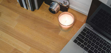 Cropped shot of comfortable office room with laptop computer, office supplies and candle on wooden table background