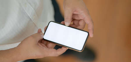 Close-up view of young businessman touching blank screen smartphone while standing in office room 스톡 콘텐츠