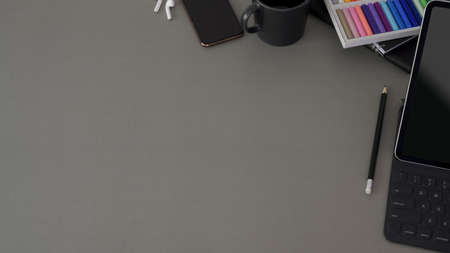 Top view of modern workplace with copy space and office supplies on dark grey background 스톡 콘텐츠