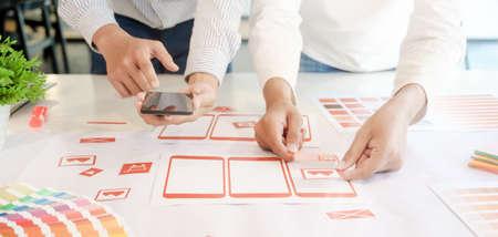 Ausgeschnittene Aufnahme eines jungen professionellen UX-Grafikdesignerteams, das die Smartphone-Vorlagen im Büroraum entwickelt