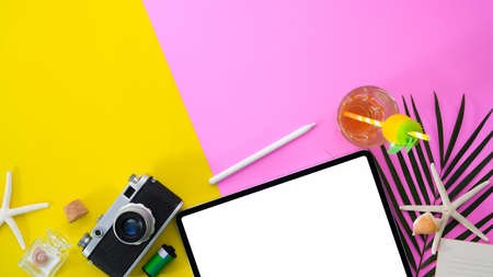 Top view of colourful summer workspace with blank screen tablet and office supplies on pink and yellow desk background Фото со стока
