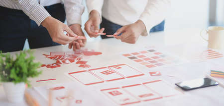 Close-up view of young professional UX web developer team working on smartphone template together