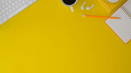Top view of modern workplace with office supplies and copy space on yellow and desk background