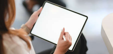Cropped shot of young businesswoman using blank screen tablet in modern office room