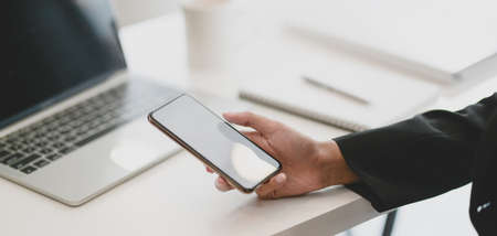 Cropped shot of young businesswoman using blank screen smartphone in modern office room