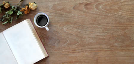Top view of comfortable workplace with open notebook, coffee cup and copy space on wooden table