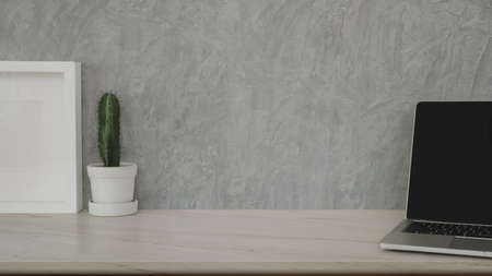 Cropped shot of stylish workplace with copy space and office supplies on marble desk and grey wall background Фото со стока