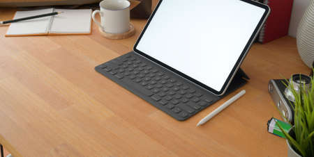Cropped shot of comfortable workplace with blank screen digital tablet and office supplies on wooden table