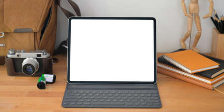 Close-up view of professional workplace with blank screen digital tablet and office supplies on wooden table