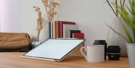 Close-up view of professional photographer workspace with mock up tablet and office supplies on wooden table  스톡 콘텐츠