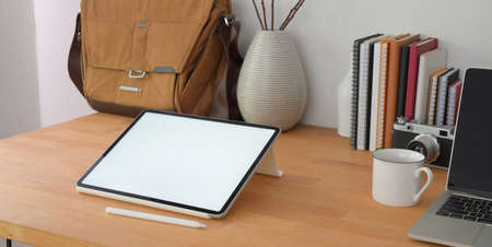 Cropped shot of comfortable office room with blank screen digital tablet on wooden table