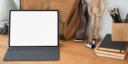 Blank screen digital tablet in comfortable photographer workplace with office supplies on wooden table  스톡 콘텐츠