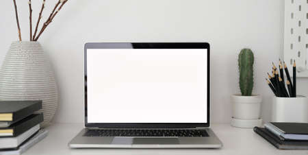 Close-up view of stylish workplace with open blank screen laptop computer and office supplies on white table