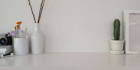 Cropped shot of minimal workplace with paint tools and office supplies on white table and white wall background