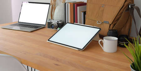 Close-up view of cozy photographer workspace with mock up digital tablet and laptop computer with office supplies on wooden table desk