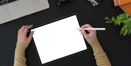 Top view of young woman working on her project with blank screen tablet and office supplies