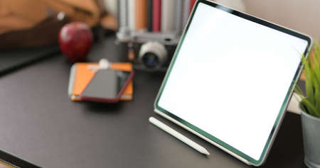 Cropped shot of stylish workplace with blank screen digital tablet and office supplies on black table background