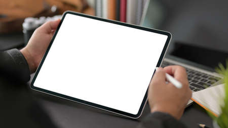 Cropped shot of young businessman using blank screen digital tablet in modern office room