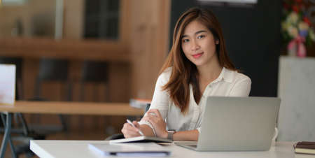 Portrait of young beautiful asian businesswoman working on her project with laptop computer and smiling to the camera