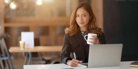 Portrait of beautiful asian businesswoman working on her project with laptop computer and drinking coffee in the office room