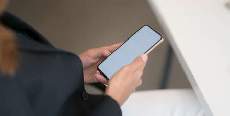 Cropped shot of young businesswoman working with blank smartphone in office room  스톡 콘텐츠