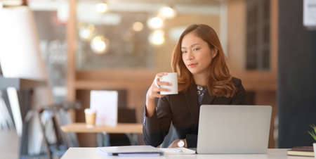 Portrait of beautiful asian businesswoman drinking coffee while working on her project with laptop computer in the office room