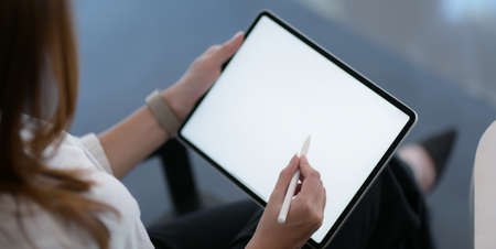 Cropped shot of businesswoman working on her project with blank screen digital tablet in modern workplace  스톡 콘텐츠